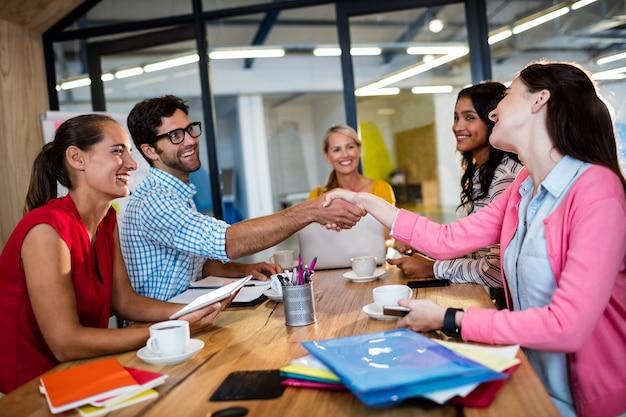 握手を与えるカジュアルなビジネスチーム