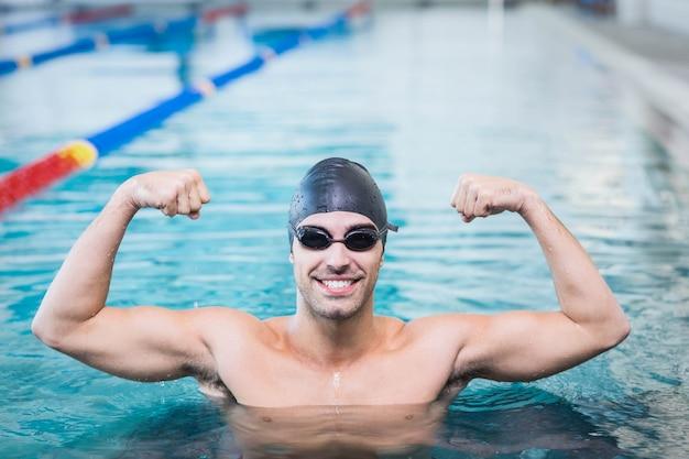Красивый мужчина торжествует с поднятыми руками в бассейне