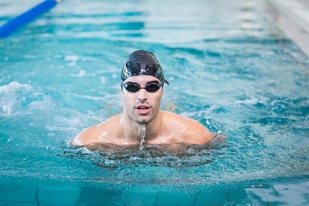 プールで泳いでいるハンサムな男