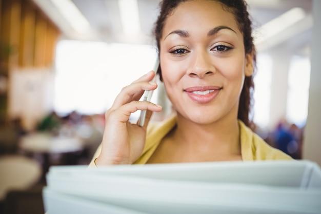 カフェテリアで携帯電話を使用しながらファイルを保持している実業家の肖像