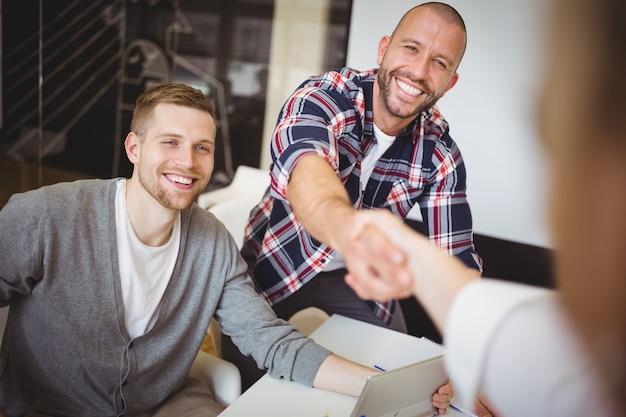 Деловые люди пожимают друг другу руки в креативном офисе