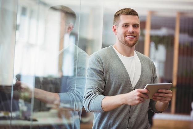 Бизнесмен держа цифровую таблетку в офисе