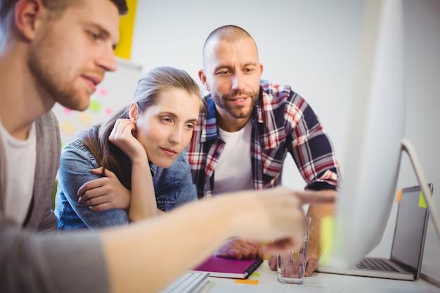オフィスで同僚とコンピューターで指している実業家