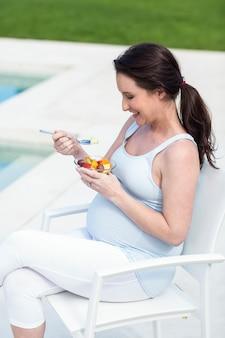 スイミングプールのそばの果物を食べて笑顔の妊娠中の女性