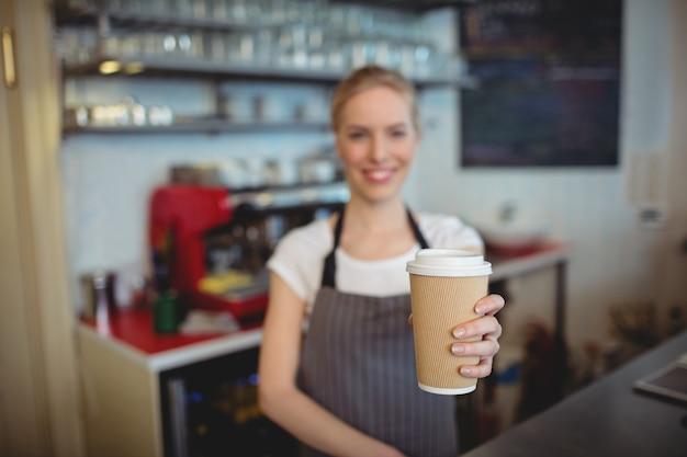 Портрет бариста, держа чашку кофе в кафе