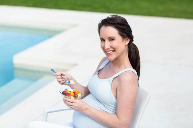 スイミングプールのそばの妊娠中の女性を笑顔の肖像画