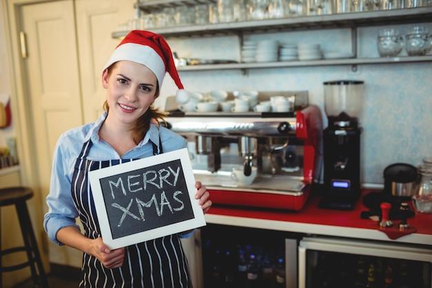 Портрет бариста с табличкой на рождество в кафе