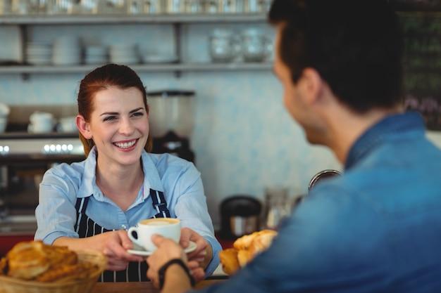 カフェテリアで顧客にコーヒーを与える陽気なバリスタ