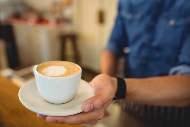 Крупный план свежего кофе, поданного бариста в кафе