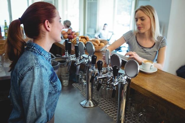 カフェで顧客と話しているバリスタ