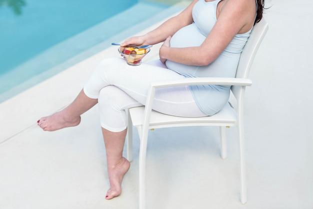 妊娠中の女性がプールのそばの果物を食べる