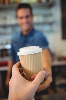 Крупный план клиента, принимающего кофе от бариста в кафе