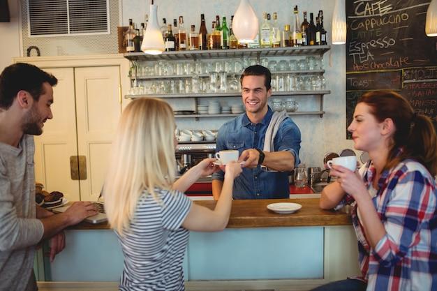 Красивый официант, подающий кофе клиенту с друзьями