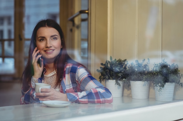 カフェで携帯電話を聞いて幸せな女
