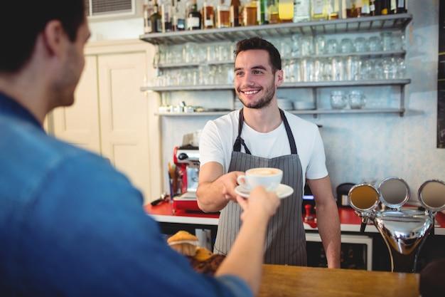 カフェで顧客にコーヒーを与える幸せなウェイター