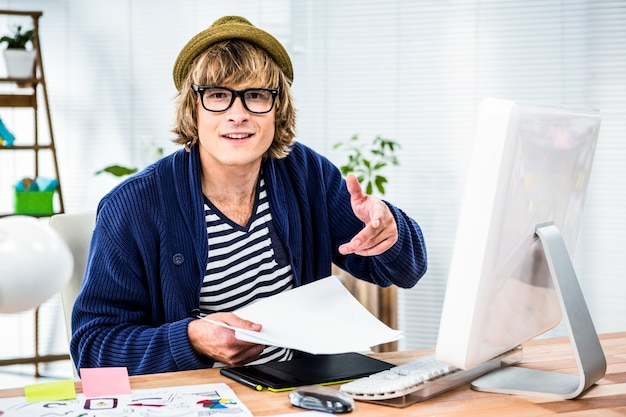 彼の机で働いて笑顔の流行に敏感なビジネスマン