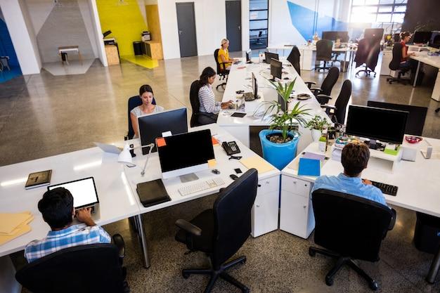 オフィスでコンピューターを使用しているカジュアルな同僚