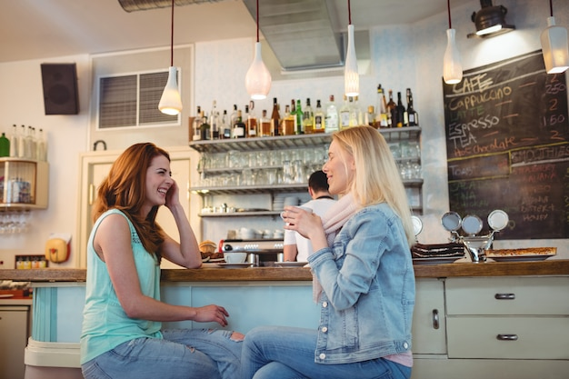 コーヒーショップのカウンターで話している幸せな友達