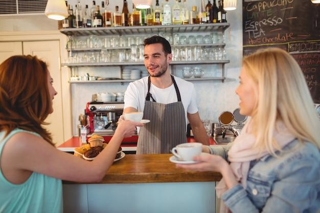 Счастливая бариста, подающая кофе женщине в кафе
