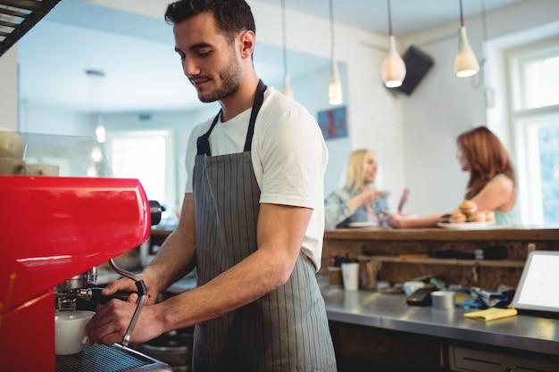 カフェでコーヒーメーカーを使用して自信を持ってバリスタ