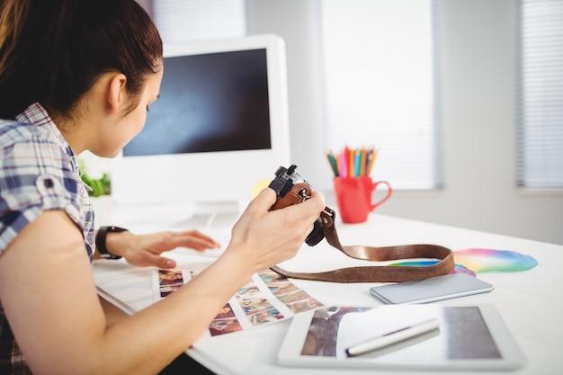 Женщина держит камеру в офисе