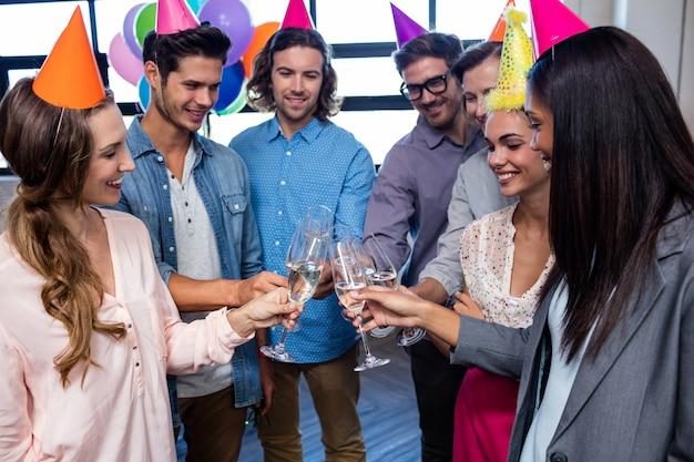 誕生日を祝うためにシャンパンを飲んで幸せな同僚