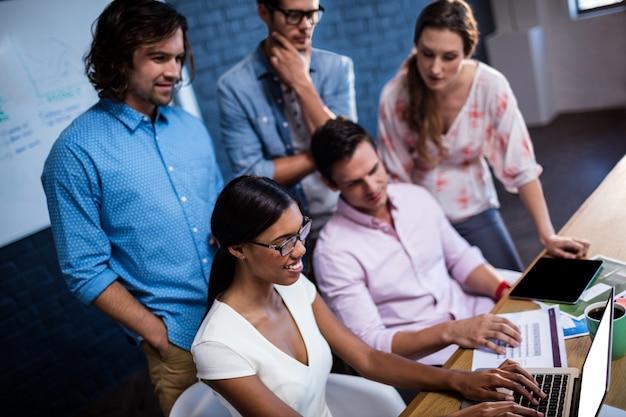 ノートパソコンを見ている同僚のグループ