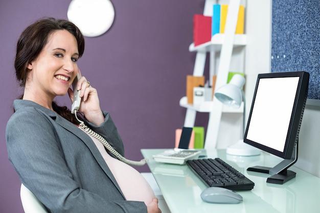 Беременная женщина по телефону в офисе