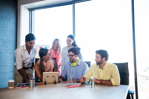 Группа сотрудников с помощью планшетного компьютера