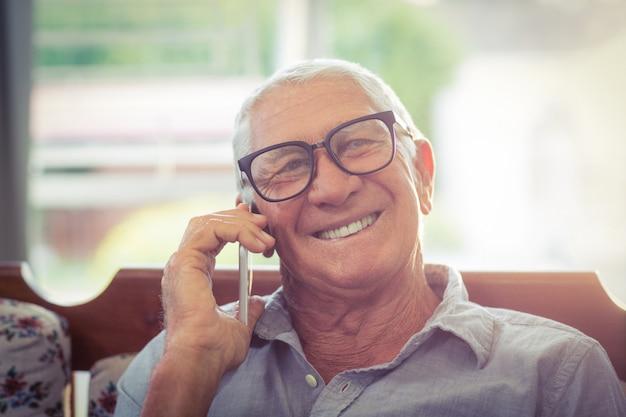 年配の男性が携帯電話で話しています。
