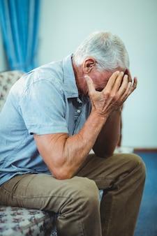 Старший мужчина страдает от головной боли