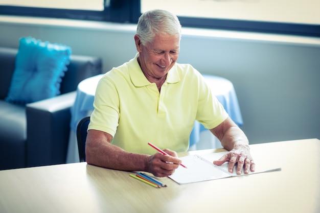 Старший мужчина, рисование цветным карандашом в книге рисования