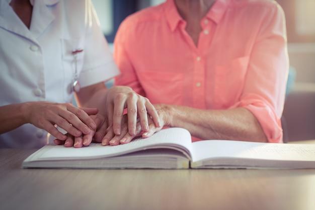 Женщина медсестра помогает пациенту читать книгу брайля