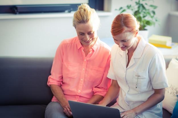 Женская медсестра и старшая женщина, используя ноутбук