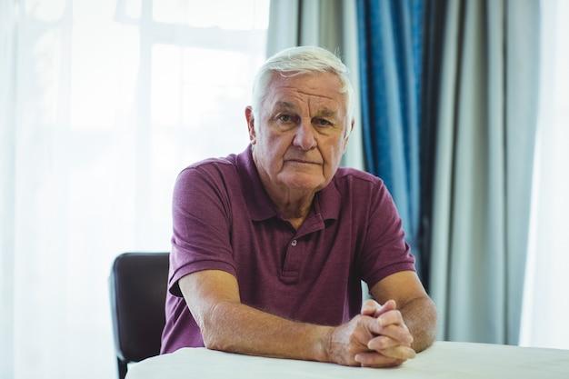 テーブルの横に座っている心配している年配の男性