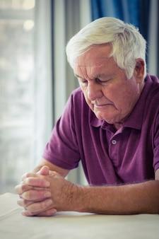 リビングルームで祈っている年配の男性