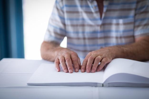 Слепой человек читает книгу брайля
