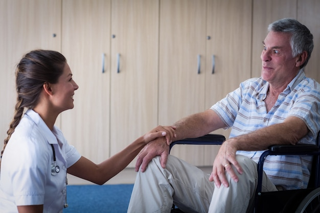 Женский доктор утешая старшего человека в живущей комнате