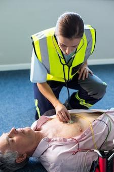 Фельдшер осматривает больного во время сердечно-легочной реанимации