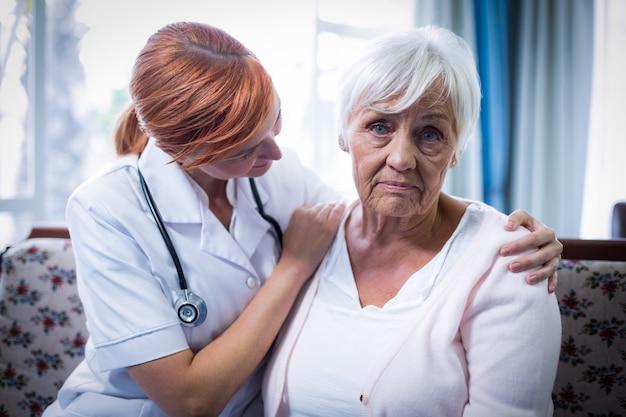 Доктор утешая старшую женщину