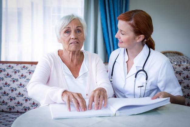 Женщина-врач помогает слепому пациенту читать книгу брайля