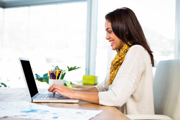 若い女の子はオフィスで彼のコンピューターを使用します