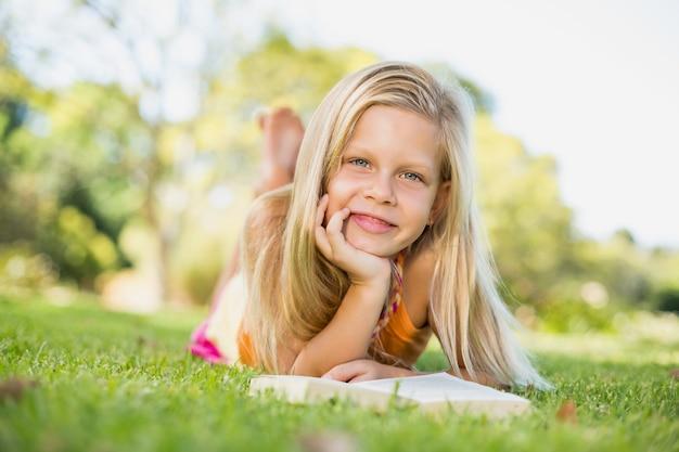 本と草の上に横たわる少女