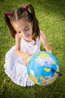 Девушка смотря глобус