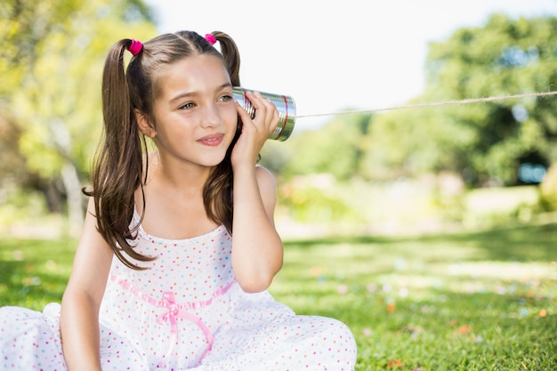 ブリキ缶電話を聞いている若い女の子