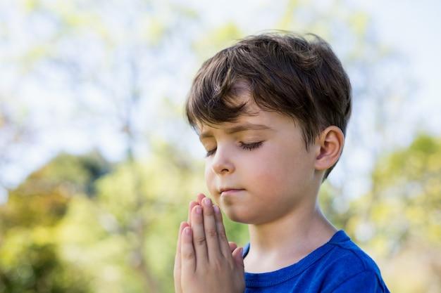 目を閉じて祈る少年
