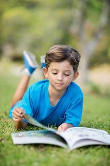 Молодая книга чтения мальчика в парке