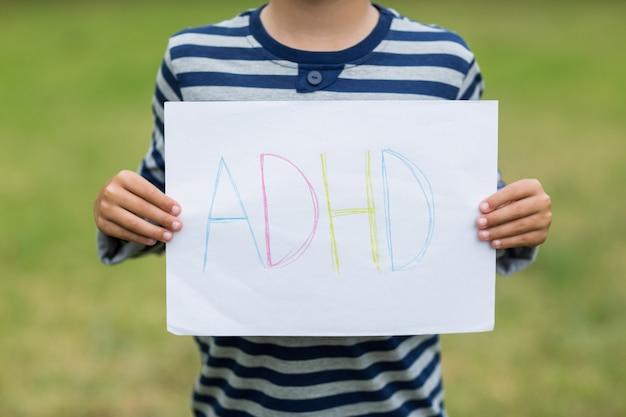 アルファベットを読むプラカードを持って公園の少年