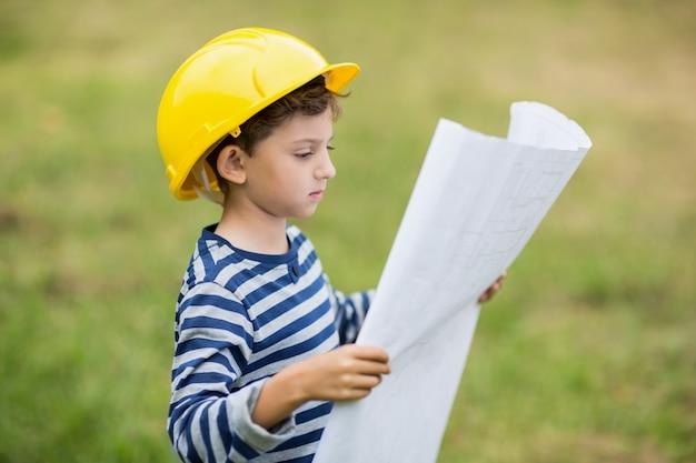 計画を読んでハード帽子の少年