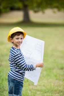 Мальчик в каске держит план